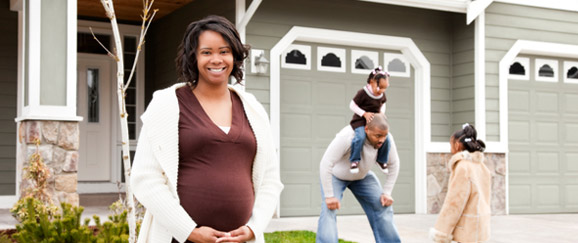 pregnant woman smiling in front of house